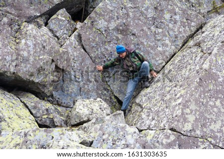 Southern Urals. A mature tourist makes an ascent to the top along a large stone placer. #1631303635