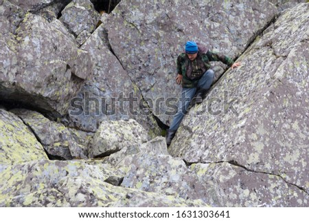 Southern Urals. A mature tourist makes an ascent to the top along a large stone placer. #1631303641