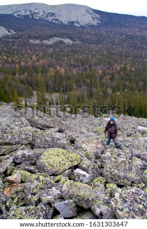 Southern Urals. A mature tourist makes an ascent to the top along a large stone placer. #1631303647