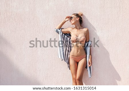 Slim woman in beige bikini and striped shirt posing against pink wall in summer sunny day. Fashion look for the beach vacations.