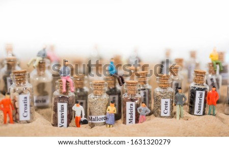 Glass test-tube with sand of different summer vacation destinations. Located in sand with small people figures. #1631320279