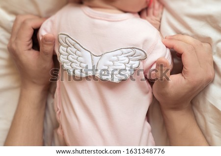 hands of a parent hug a newborn baby in pink clothes with angel wings on his back, parental care for a newborn baby #1631348776