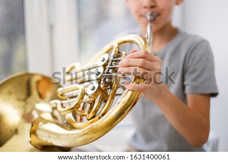 Caucasian boy learns to play the horns, a child plays a wind musical instrument. Light window, real interior. Royalty-Free Stock Photo #1631400061