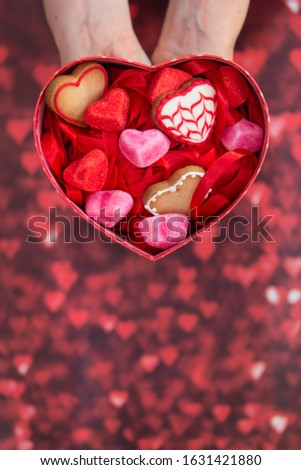 heart-shaped box, with heart-shaped jelly beans, heart-shaped cookies and red background #1631421880