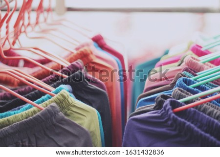 close up clothes hang on clothes rack in clothing store with colorful tone   #1631432836
