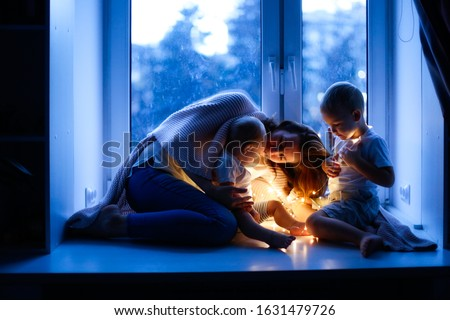 European family, mother with two children at the window, evening mood and authentic photo. brother and sister with mom with a garland on the window #1631479726