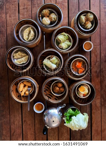 Dim sum stock photo. Cantonese style of steamed dumpling in small, almost bite-sized portions wit variety of fillings. Chinese cuisine restaurant experience. Best for menu, cafe or blog decoration.