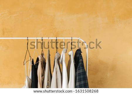 wardrobe, hanger with clothes on yellow background ,pastel color clothes, female clothes on open clothes rail #1631508268