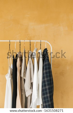 wardrobe, hanger with clothes on yellow background ,pastel color clothes, female clothes on open clothes rail #1631508271