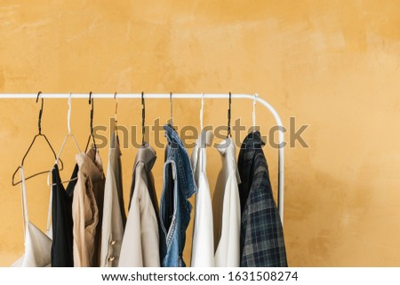 wardrobe, hanger with clothes on yellow background ,pastel color clothes, female clothes on open clothes rail #1631508274