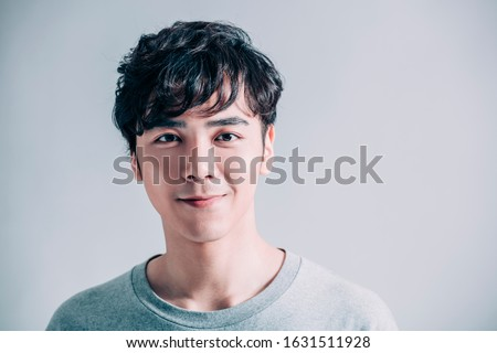 portrait of young smiling handsome man isolated on gray background Royalty-Free Stock Photo #1631511928