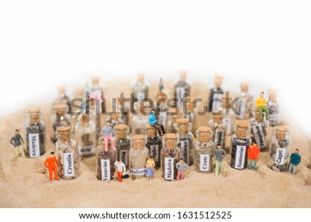 Glass test-tube with sand of different summer vacation destinations. Located in sand with small people figures. #1631512525