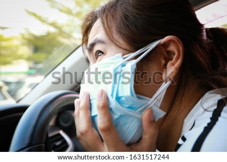 Stressed asian woman with protection masks of many layers,worried about inhaling toxic fumes,afraid of air pollution,PM 2.5,smog,dust,anxiety female people wearing multiple layers of medical face mask