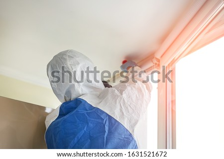 Man wearing protective biological suit and gas-mask due to mers coronavirus global pandemic warning and danger. Worker make disinfection, pest control and mold removal and ventilation at house room Royalty-Free Stock Photo #1631521672
