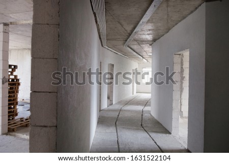 Long light floor corridor in a new building. Completed apartments without repair from the builder. Final step Construction house of foam block white walls. Stock Photo Finished Real estate.