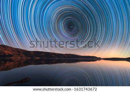 Beautiful night landscape with small lake and mountains. The colorful star trails on the sky reflacted on the water. Night time lapse photography.