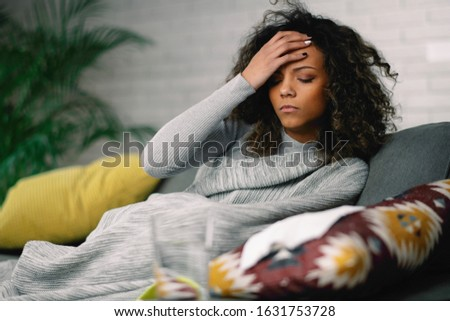 Young sick woman at home. African woman lying on sofa having fever.  Royalty-Free Stock Photo #1631753728