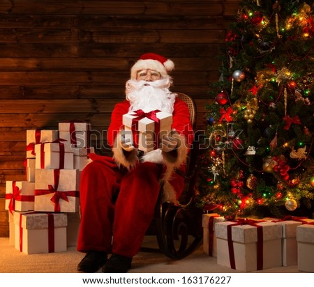 Santa Claus sitting on rocking chair in wooden home interior presenting gift box #163176227