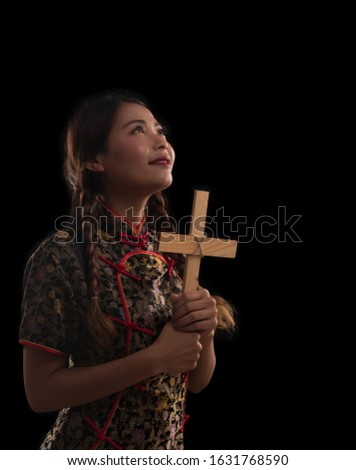 Vertical picture of Chinese lady holding wooden cross or crucifix in hands, looking up with faith in god. Catholic or Christian woman in Chineses dress isolated on black background.