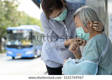 Asian woman wearing medical face mask for senior person because sick female elderly with cough and fever,prevent spread of germs to other people at bus stop, Coronavirus,MERS-CoV,Wuhan Virus 2019-nCoV #1631769967