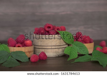 ripe fresh raspberries in three wooden bowls on a wooden background close-up. background with raspberry berries and raspberry leaves. #1631784613