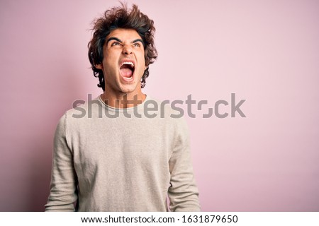 Young handsome man wearing casual t-shirt standing over isolated pink background angry and mad screaming frustrated and furious, shouting with anger. Rage and aggressive concept. Royalty-Free Stock Photo #1631879650