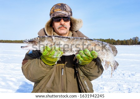 man holds a catch, a large fish pike. Winter, winter sports winter fishing #1631942245