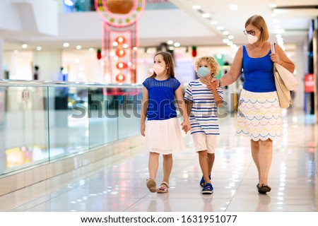 Family wearing face mask in shopping mall in Asia. Mother and children wear facemask during coronavirus and flu outbreak in China. Virus and illness protection. Kids in masks in public crowded place. #1631951077