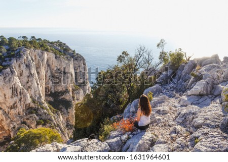 Mediterranean blue sea in the Calanques National Park - Marseille - France. A girl enjoying the view with orange light. Carbonate rocks and calm blue sea. #1631964601