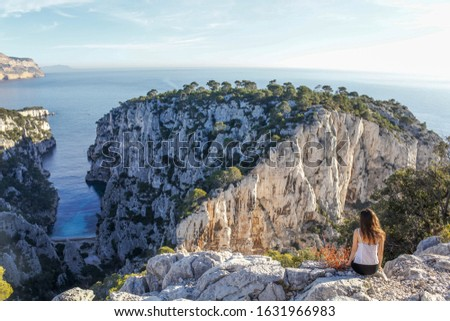 Mediterranean blue sea in the Calanques National Park - Marseille - France. A girl enjoying the view in orange blue light. White carbonate rocks and calm blue sea water. #1631966983