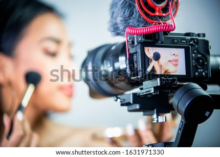 Beautiful young woman doing make-up in from of the camera, make-up tutorial