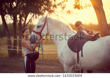 Man putting a saddle on a horse, while woman puts on the reins . Training  and fun on countryside, sunset golden hour. Freedom nature concept.  #1632033604