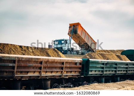 Loading railway wagons with stone, a tractor loads wagons with stone, transporting rubble on a railway #1632080869