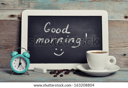 Cup of coffee with blackboard and alarm clock on vintage wooden background