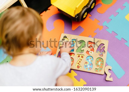 child on the carpet collects a puzzle of numbers, learns to count and learns numbers. Concept of learning by playing for toddler development #1632090139