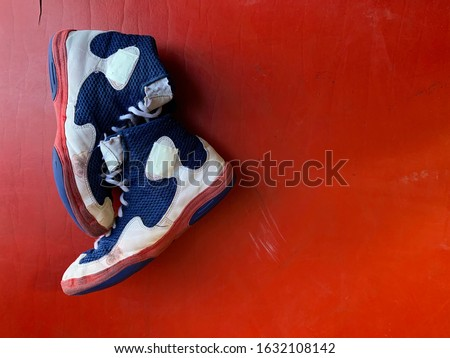Wrestling shoes on a red mat with an overhead view.