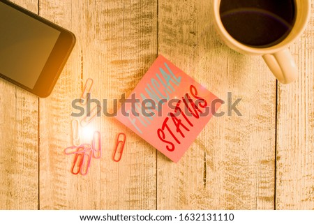 Text sign showing Financial Status. Conceptual photo level of income into which applicants are categorized Stationary placed next to a cup of black coffee above the wooden table. #1632131110