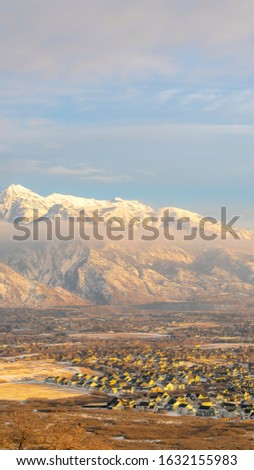 Photo Vertical Mount Timpanogos and neighborhood houses under cloudy and foggy sky in winter #1632155983
