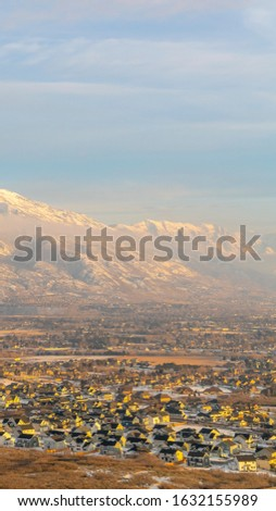 Photo Vertical Mount Timpanogos and neighborhood houses under cloudy and foggy sky in winter #1632155989