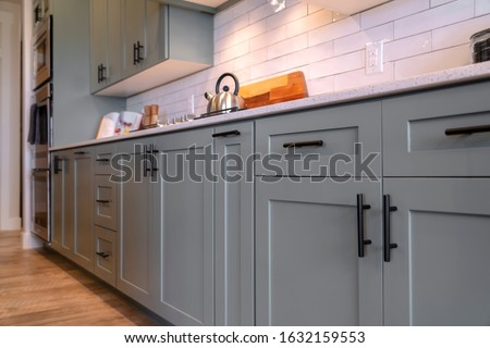 Kitchen cabinets with white countertop black handles and tile backsplash Royalty-Free Stock Photo #1632159553
