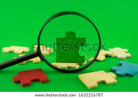 Colorful jigsaw puzzle pieces with magnifying glass focused on a single green corner piece in a conceptual image over green for search, investigation and problem solving #1632216787
