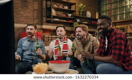 Excited cheerful group of men attentively watching tv match, cheering up for team, drinking beer, expecting on victory. Celebrating successful game. Home party, friendship concept, hanging out #1632270334
