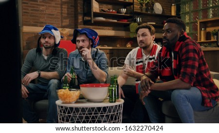 Four cheerful male football fans cheering for their teams at home by the TV with football attributes. Standoff, true friendship, entertainment concept. Home party, drinking beer, eating snacks by tv #1632270424