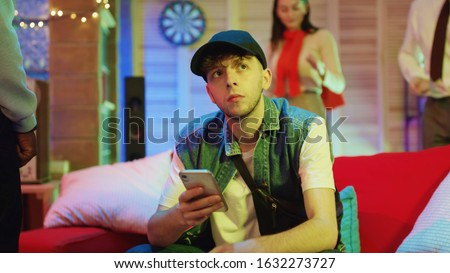Bored modern guy using a smartphone browsing social network while his friends having fun party hangout at home. Man outsider. Concept of nomophobia. #1632273727