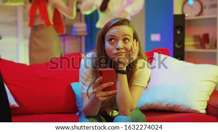 Young girl outsider sitting on sofa with smartphone browsing social network getting bored while her friends dancing and having fun on party. #1632274024