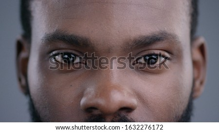 Close-up of beautiful black man eyes staring at camera. Portrait detail of serious confident african american man. Royalty-Free Stock Photo #1632276172