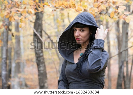 Brunette girl in a grey dress holding her hood. With serious expression and penetrating look. In a forest in autumn. Concept of emotions. #1632433684