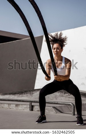 Fitness young afro girl exercising with battle ropes at outdoors. Woman training doing battling rope workout working out arms and cardio for cross fit exercises #1632462505
