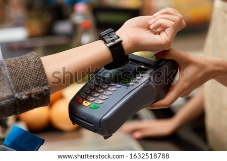 Young woman standing at the supermarket at cashier checkout counter paying for purchases contactless with smartwatch applying on reader doing daily shopping close-up #1632518788
