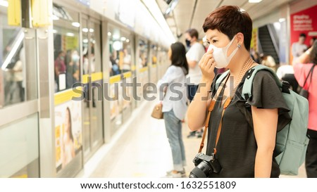 Beautiful middle aged Asian female traveller cover mouth and cough, wear medical face mask to protect from infection of viruses, pandemic, outbreak and epidemic of disease in crowded underground train #1632551809